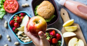 Sandwich, strawberries and peanuts in lunchboxes, hand holding an apple