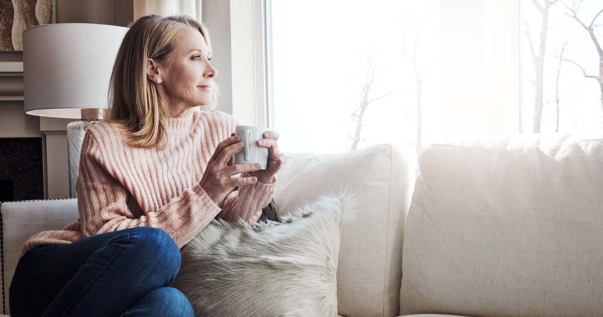 Mature woman relaxing on the sofa at home with a cup of coffee