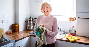 Senior woman looking happy as she stands in her kitchen drying dishes