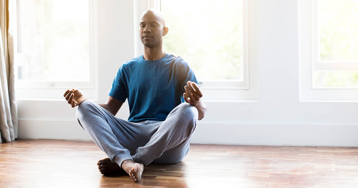 Man practicing yoga in lotus position at home
