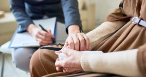 Psychologist holding hand of senior woman during therapy session