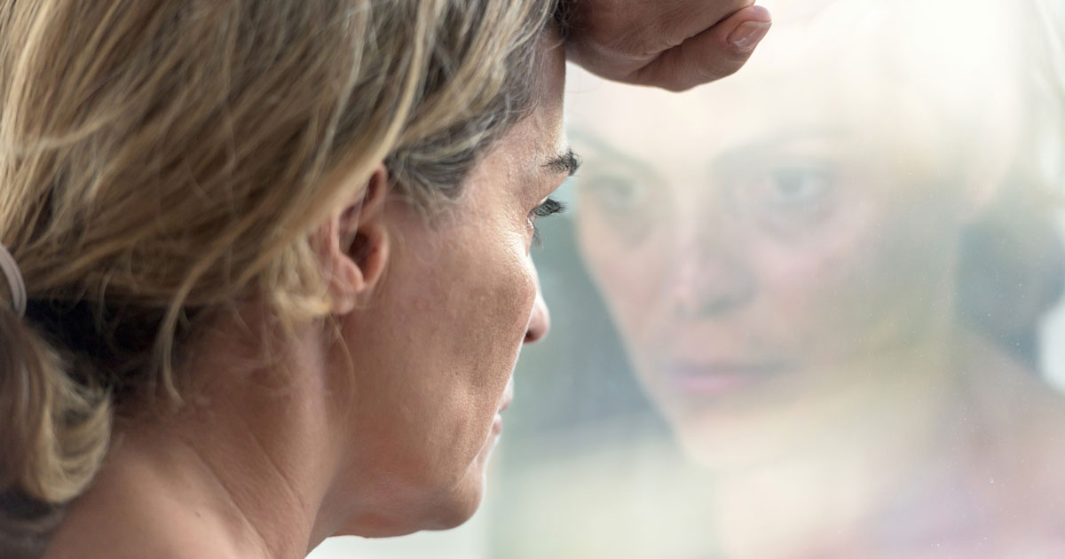 Depressed woman looking out window