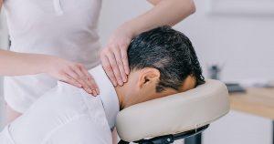 Close-up shot of masseuse doing neck massage on man