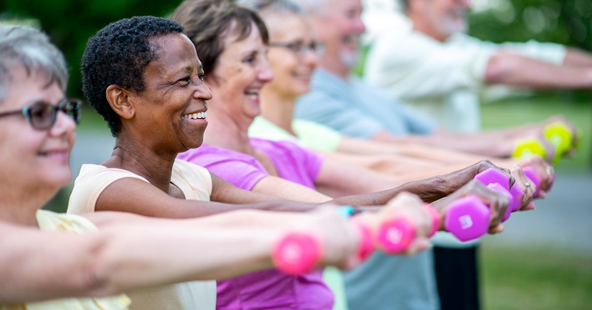 A group of senior men and women are outdoors in a park, exercising with light dumbbells