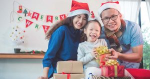 Girl and her parents open christmas gift boxes at home
