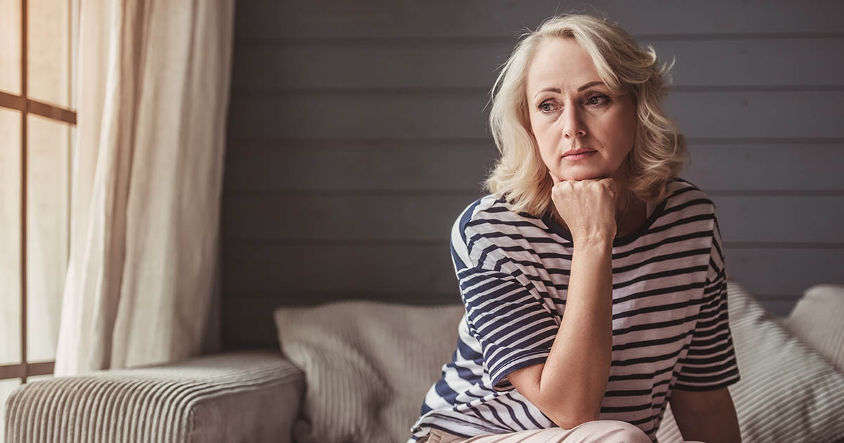 Sad senior woman is leaning on her hand and looking downward while sitting on couch at home