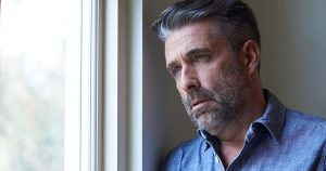 Mature man suffering from depression looking out of window