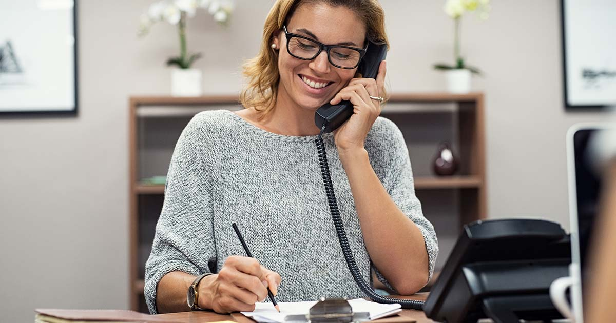 Business woman sitting at her desk making telephone call and taking notes on notebook