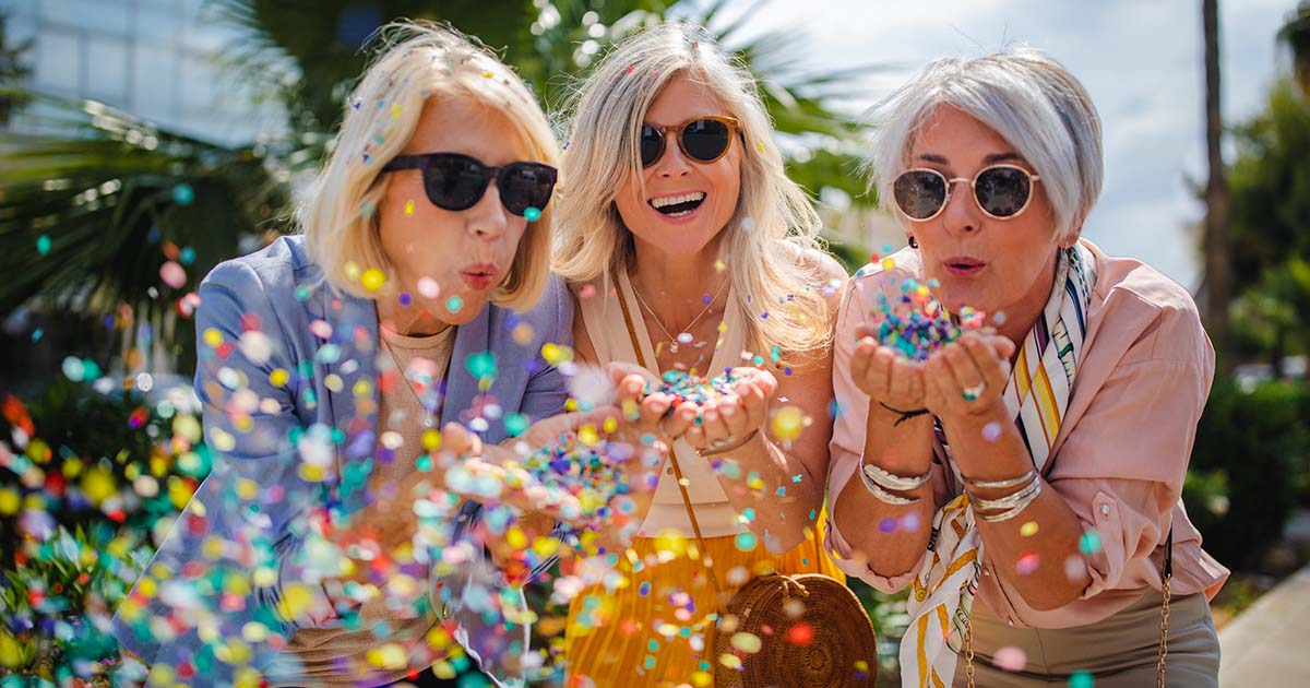 Mature friends having fun and celebrating by blowing colorful confetti in city street