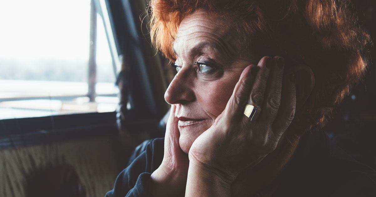 Upset woman looking out window